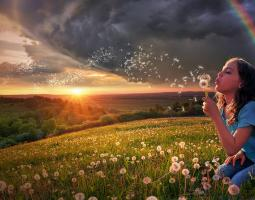 Photo of girl in a field with a rainbow and dandelions.