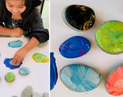 Child doing a colorful art project with paint and rocks