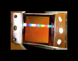 Photo of a rainbow pattern of diffracted visible light in front of a honeycomb pattern panel.