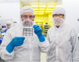 Two scientists wearing white lab jumpers in a lab; the male on the left is wearing blue rubber gloves and holding an array prototype that looks like a small grid.