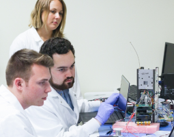Photo of three scientists (1 female, 2 male) working on Q-PACE electronics at a desk.