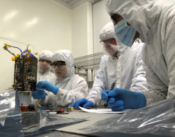 Photo of scientists in lab assembling equipment