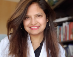 Portrait photo of smiling woman with long dark hair wearing a white lab coat