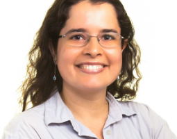 Portrait photo of smiling woman wearing glasses and with dark curly hair