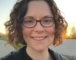 Portrait photo of smiling woman with short curly hair wearing glasses