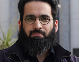 Portrait photo of a dark bearded man wearing dark clothing and glasses