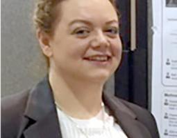 Portrait photo of a smiling woman with red hair and wearing a suit