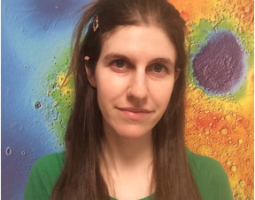 Portrait photo of woman with long brown hair wearing a green shirt standing in front of a colorful science image