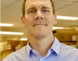 Portrait photo of a man with short light blonde hear wearing a light blue collared shirt and standing in an office space