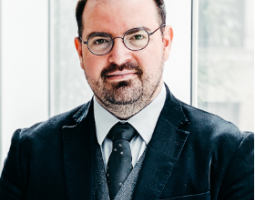 Portrait photo of a man with short dark hair and facial hair wearing glasses and a dark suit as he sits in front of a window