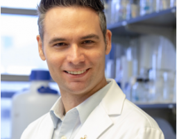 Portrait photo of a smiling man wearing a white lab coat and standing in a lab.