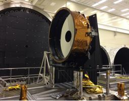 Photo of large mirror being assembled in a NASA facility.