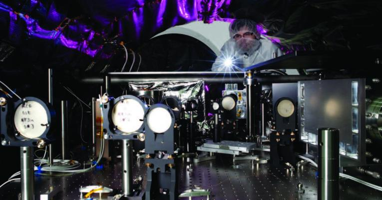 Photo of scientist looking into vacuum chamber
