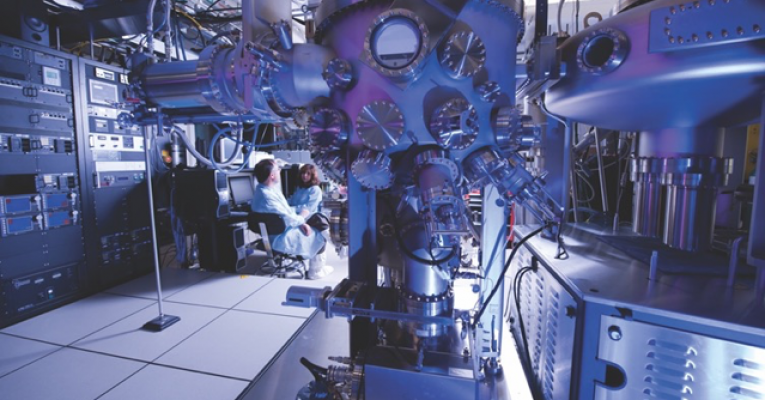 Photo of a male and female scientist is a lab full of equipment