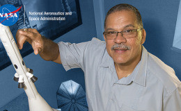 Photo of man pointing to model spacecraft