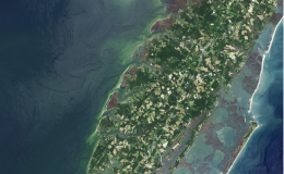 Aerial image showing green and grey peninsula of land surrounded by ocean in shades of light teal blue to dark greenish blue.