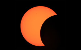 Photo of orange colored sun with black sphere eclipsing the right side