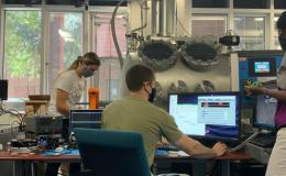 Photograph of two women and one man in a testing lab with computers and hardware on the desks