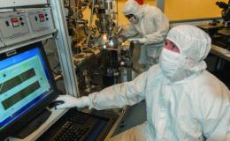 Photo of scientist in lab gear working on computer testing chips