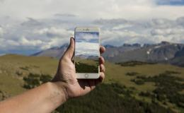 Photo of handing holding up a mobile phone taking a photo of the mountain landscape in the background.
